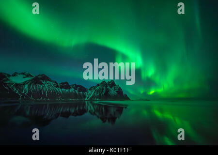 Aurora reflections on Stokksnes black beach over Vestrahorn mountains, Iceland - Stock Photo