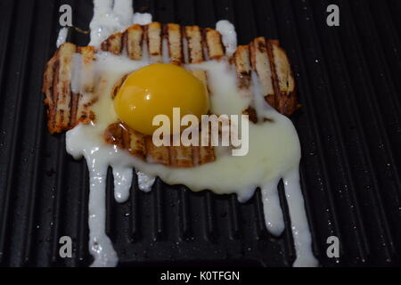Smoky bacon on a grill with egg - Stock Photo