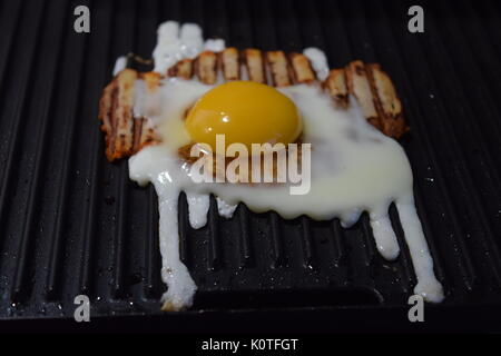 Bacon on a grill with egg - Stock Photo