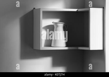 Minimalist interior of white modern kitchen. One isolated jug on shelf and light from window - Stock Photo