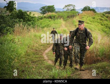 U.S. Marine Corps Sgt. Jeremy Pogue, a rifleman with 1st Battalion, 1st Marine Regiment, 1st Marine Division, hikes - Stock Photo