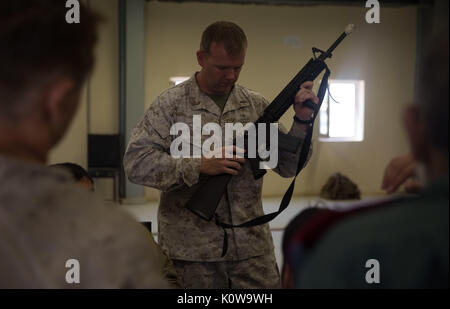 A U.S. Marine advisor with Task Force Southwest shows Afghan National Police officers how to perform a functions - Stock Photo