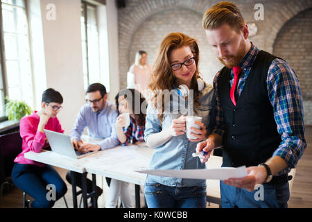 Portrait of two young perspective designers discussing - Stock Photo