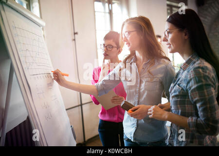 Portrait of architects discussing and drawing on board - Stock Photo