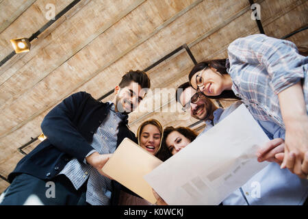 Young perspective designers looking at project schemes - Stock Photo