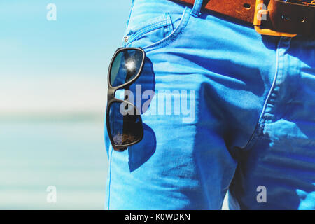 Sunglasses hanging out of front pocket on blue jeans close-up. Sunny day on the beach, part of the summer wardrobe - Stock Photo
