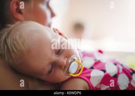 Young mother holding her sleeping newborn baby - Stock Photo