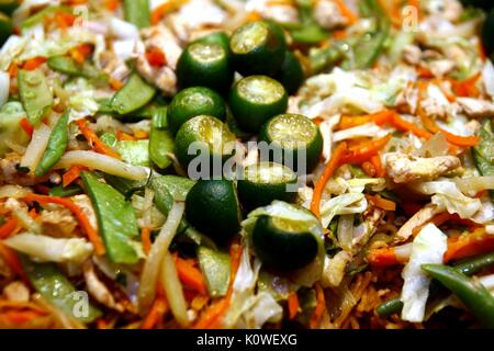 Photo of sliced Kalamansi on top of a Filipino delicacy food called Pancit Canton which is made of stir fried noodles - Stock Photo