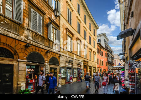 A colorful street in Rome Italy as tourists window shop and enjoy the historic downtown area - Stock Photo