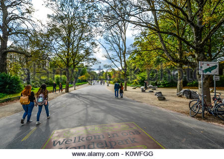 Vondelpark, large park in Amsterdam in early autumn as people walk along the path - Stock Photo