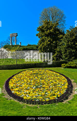 Medallion of spring flowers in the park, roman columns behind, Nyon, Vaud, Switzerland - Stock Photo
