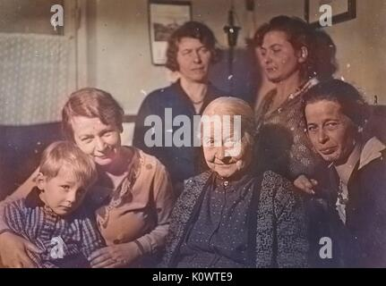 Portrait of a family in a living room, five women and a young boy posing for a family picture, Germany, 1946. Note: - Stock Photo