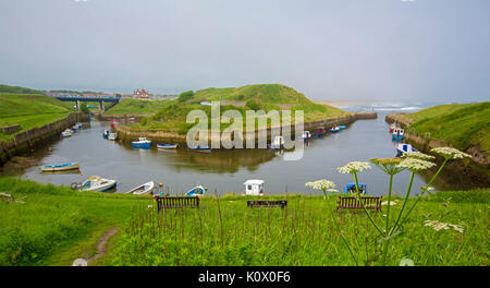 Boats moored in sheltered harbour at Seaton Sluice near coastal village of Hartley, with road bridge, town, & sandy - Stock Photo
