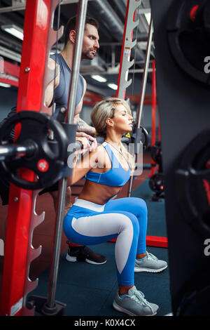 Sporty girl doing squat exercises with assistance of her personal trainer at gym. - Stock Photo