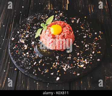 raw minced meat, vegetables with salt and spices, on a black background, selective focus, space for text - Stock Photo