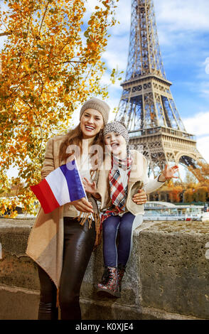 Autumn getaways in Paris with family. Portrait of happy mother and child travellers on embankment in Paris, France - Stock Photo