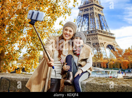 Autumn getaways in Paris with family. happy mother and child tourists on embankment near Eiffel tower in Paris, - Stock Photo