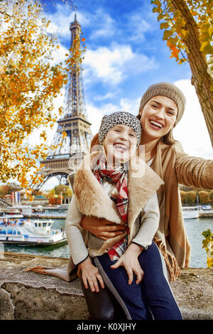 Autumn getaways in Paris with family. happy mother and child travellers on embankment near Eiffel tower in Paris, - Stock Photo