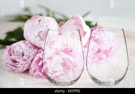 Floral mock-up of 2 stemless wine glasses, in front of a bunch of peonies, perfect for businesses who sell decals, - Stock Photo