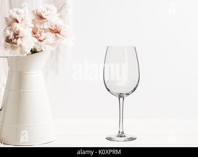 Floral mock-up of 1 wine glass next to a vase of flowers, perfect for businesses who sell decals, vinyl stickers, - Stock Photo