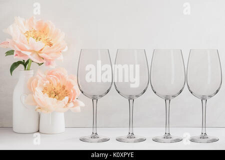 Floral mock-up of 4 wine glasses next to a vase of flowers, perfect for businesses who sell decals, vinyl stickers, - Stock Photo