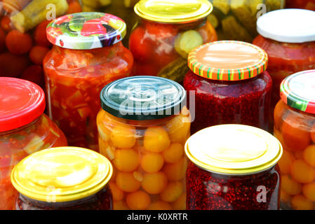 Home-made canned vegetables and jam in glass jars - Stock Photo