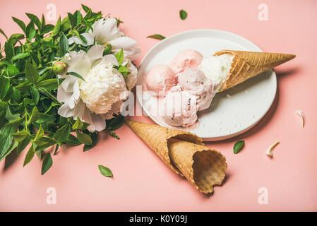 Strawberry and coconut ice cream, cones, white peony flowers - Stock Photo