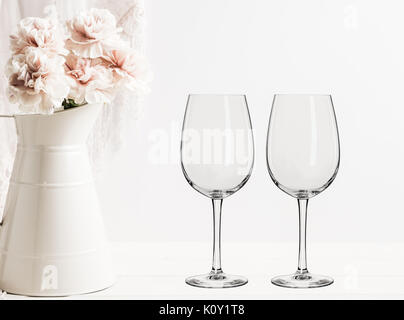 Floral mock-up of 2 wine glasses next to a vase of flowers, perfect for businesses who sell decals, vinyl stickers, - Stock Photo