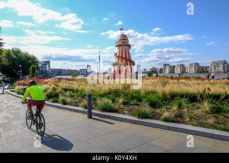 Greenwich, London, UK - August 10, 2017: Greenwich near Cutty Sark with helter skelter.  Cyclist in the foreground. - Stock Photo