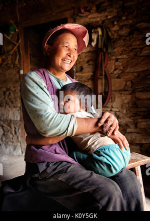 Tibetan mother and child at their traditional home in a village near Danba, Gyarong, Kham province, Tibetan plateau - Stock Photo