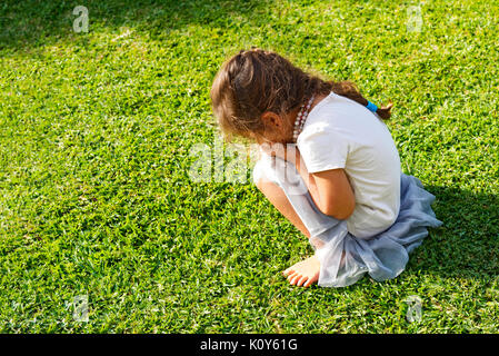 A young girl having a tantrum and crying on the lawn - Stock Photo