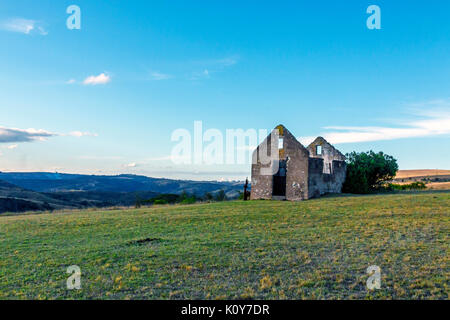Rural old abandoned derelect farm building on dry winter landscape against blue cloudy sky in Lake Eland Game reserve - Stock Photo