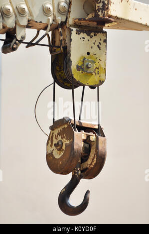 Lifting hook attached to sheave suspended by wire rope from boom of crane - Stock Photo