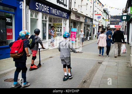 West Wales. Haverford West. Bridge Street. Clidren on scooters. - Stock Photo