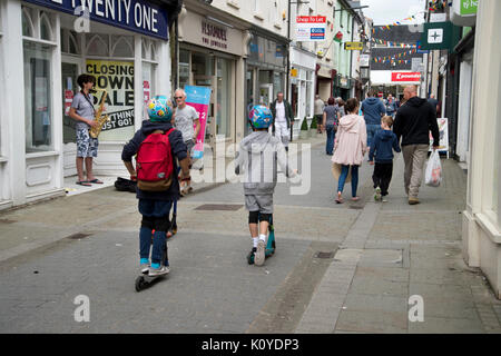 West Wales. Haverford West. Bridge Street. Children on scooters. - Stock Photo