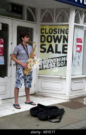 West Wales. Haverford West. Bridge Street. Busker playing a saxophone outside a closed down shop. - Stock Photo