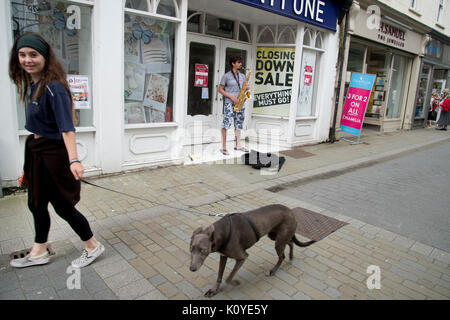 West Wales. Haverford West. Bridge Street. A young woman walking a dog and a busker playing a saxophone outside - Stock Photo