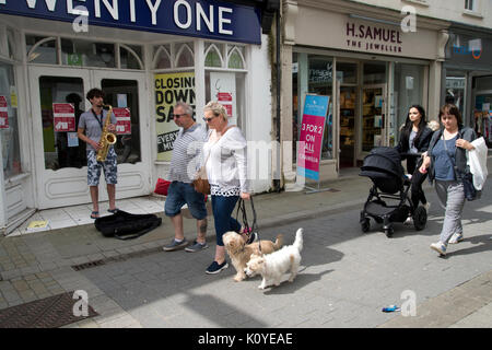 West Wales. Haverford West. Bridge Street. A couple walk down the street with their dogs whilst a busker plays a - Stock Photo