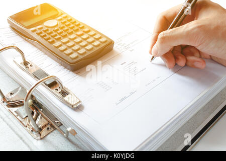 Close-up of a Businessman Analyzing Writing note accounting document with calculator at desk in office. soft focus. - Stock Photo