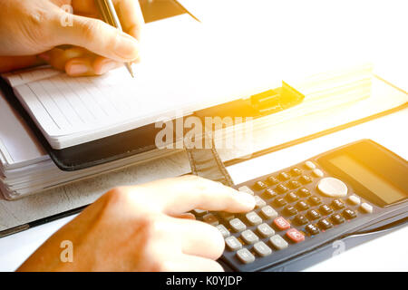 close up of man with calculator counting making notes at home, hand is writes in a notebook with books, soft focus. - Stock Photo