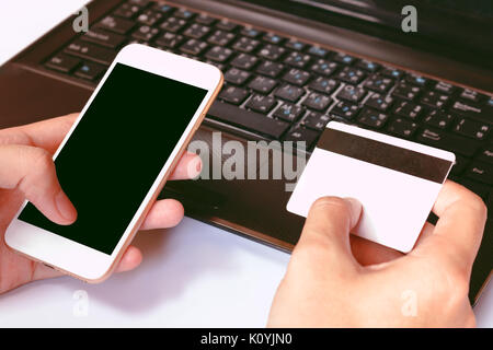 Online payment, man's hands holding a credit card over laptop and using smart phone for online shopping on the desk - Stock Photo