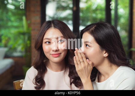 Portrait of a girl telling secrets to her amazed friend in the living room at home - Stock Photo