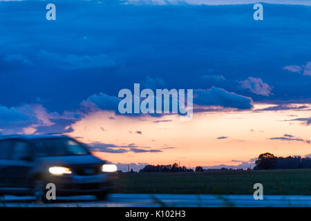 Speeding motion blur oncoming car with glowing lights on the highway after sunset. Shining the spotlight cars. Blue - Stock Photo