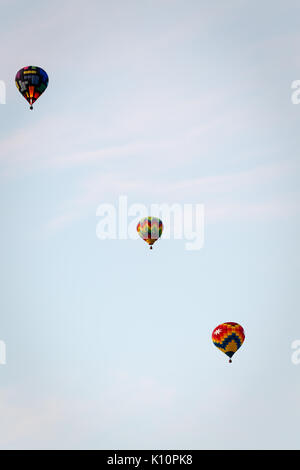 Three colorful hot air balloons float in  a row away into the sky - Stock Photo