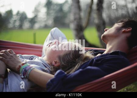 Young couple lies in a hammock - Stock Photo