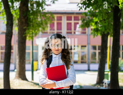 Young blue-haired girl with a backpack standing in front of school, beginning of school year, uniform, backpack, - Stock Photo