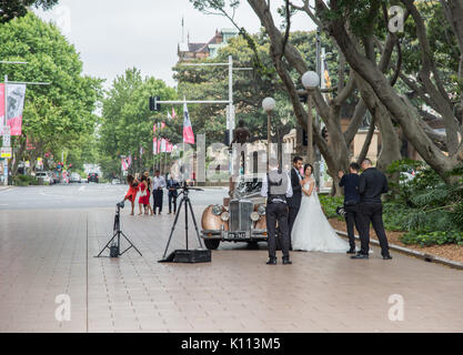 SYDNEY,NSW,AUSTRALIA-NOVEMBER 19,2016: Bride, groom, wedding party and antique car with photographer at Hyde Park - Stock Photo