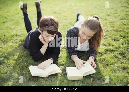 Two young women reading in a park - Stock Photo