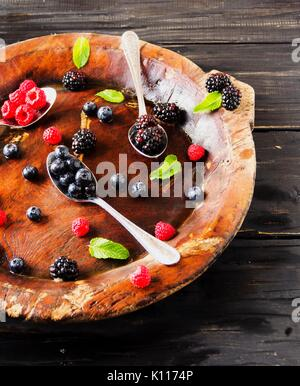 fresh ripe berries raspberries blackberries and blueberries on a brown wooden plate with a spoon on a black wooden - Stock Photo