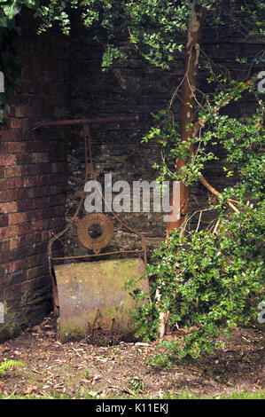 A rusty old lawn roller against an old garden wall made of bricks and covered in weeds and ivy unused and drelict - Stock Photo